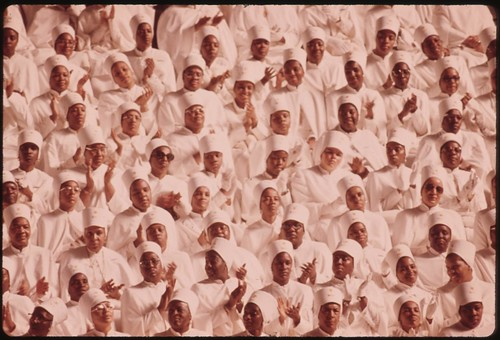15-0673MBlack Muslim Women Dressed In White Applaud Elijah Muhammad During The Delivery Of His Annual Savior's Day Message In Chicago, 03/1974