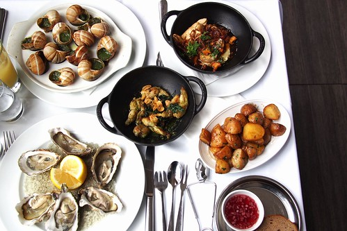 oysters, escargot snails, sweetbreads, frog legs, roast potatoes at the restaurant of Hotel du Louvre. Paris, France