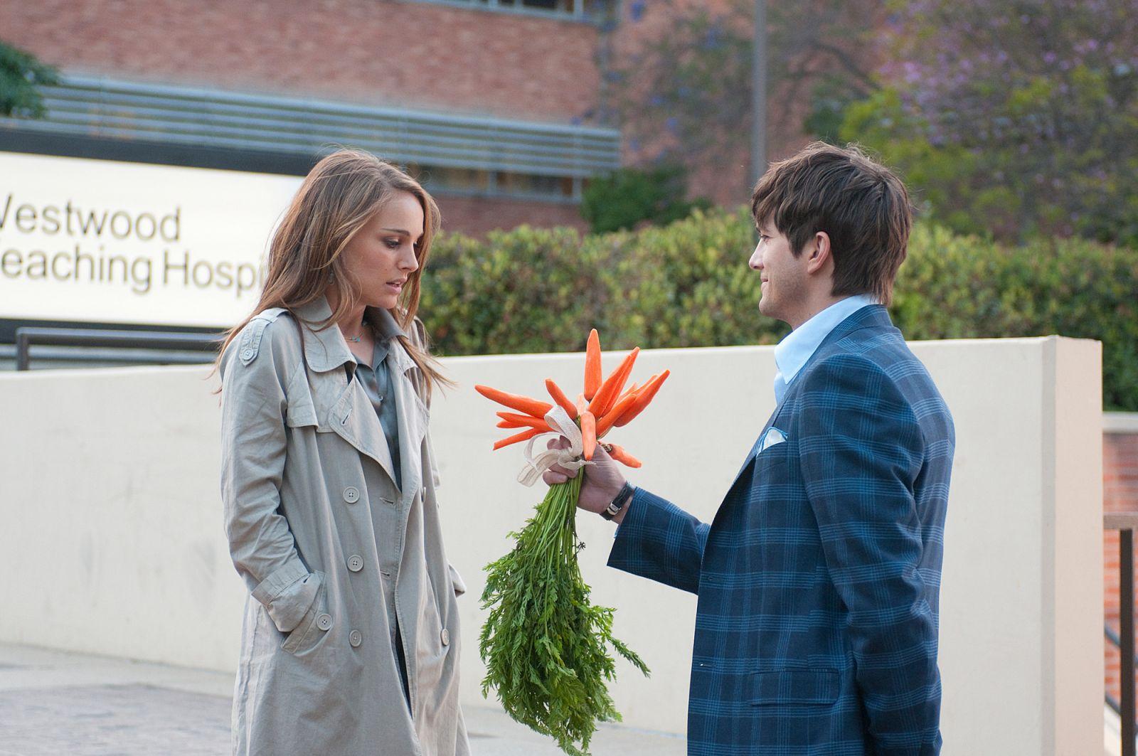 Uma mulher interpretada por Natalie Portman, com cara de surpresa, recebe um buquê de cenouras de um moço feliz, interpretado por Ashton Kutcher