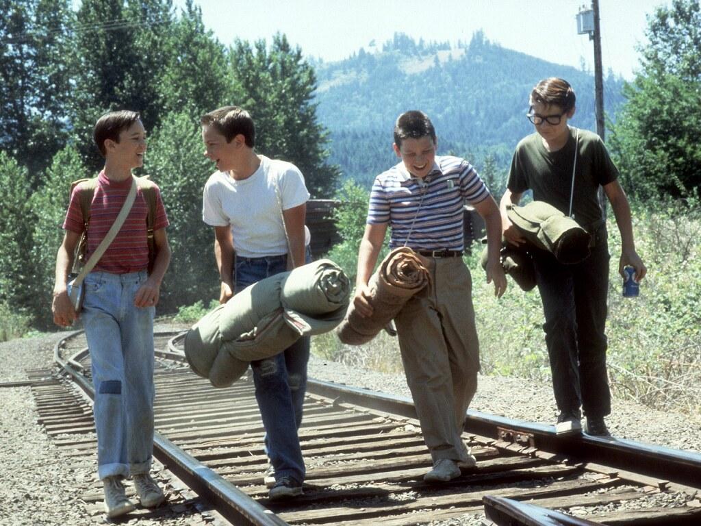 Quatro amigos pré adolescentes dos anos 60 caminham rindo sobre os trilhos adentrando uma floresta Cada um carrega uma bagagem para acampar