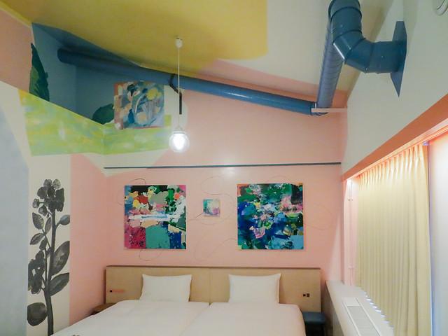 宇加治志帆コンセプトルーム ベッドの上の壁面には、平面作品が飾られているが、壁面や天井には直接ペインティングされている。面をまたいで色が塗られているため、より絵画にくるまれているように感じる。 ダクトなどへの立体物へのペインティングは、絵画からオブジェが飛び出したような効果をもたらしている。